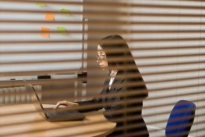 Woman workng in office, view through blinds